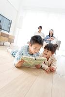 寝転んで本を読む兄と妹