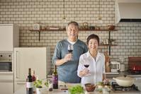 ワインを飲みながら料理をする日本人シニア夫婦