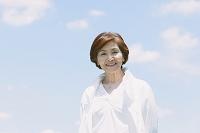 空と笑顔の日本人のシニア女性