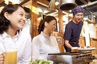料理を運ぶ居酒屋店員と笑顔の日本人女性客