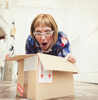 段ボール箱を開けて驚いた表情の女性