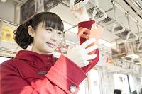 電車でスマートフォンを操作する日本人女性