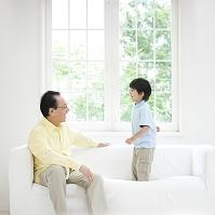 ソファで寛ぐ祖父と孫