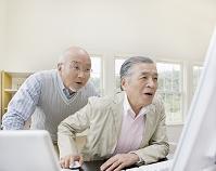 パソコンを覗き込むシニアの日本人男性