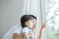 息子に窓の外を見せる父親