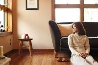 ソファにもたれて座る日本人女性