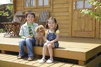 ログハウスの前に座る男の子と女の子と犬
