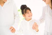両親と手を繋ぐ笑顔の女の子