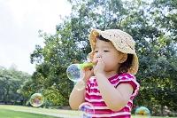 公園でシャボン玉を吹く日本人の女の子