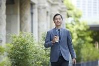 飲み物を持つ日本人ビジネス男性
