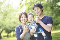 新緑の公園で赤ちゃんを抱く両親