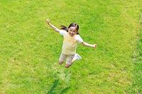 新緑の中ジャンプする6歳の日本人の女の子