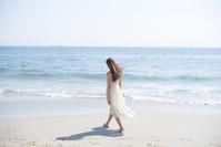 海の砂浜を素足で散歩する日本人女性