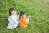 草原に座り振り返る姉弟