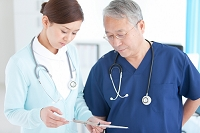 カルテを見る医師と看護師