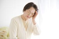 こめかみを押さえる年配の日本人女性