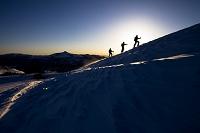 早朝に雪山を登るスキーヤー3人
