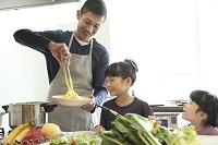 料理をする父親と幼い女の子きょうだい