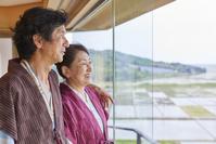 客室から眺めを楽しむ日本人シニア夫婦