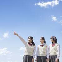 青空の下に立つ女子中学生