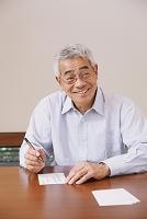 年賀状を書くシニアの日本人男性