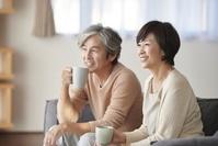 ソファでくつろぐ日本人シニア夫婦