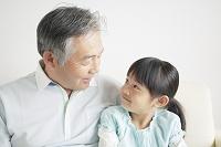 ソファに座り見つめ合う笑顔の孫と祖父