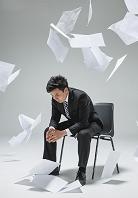 舞い散る書類の中で落ち込む日本人ビジネスマン