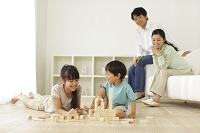 リビングで積み木遊びをする子供と見守る両親