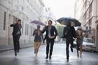 傘をさして走る外国人ビジネスグループ