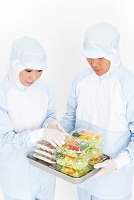食品を調べている食品衛生服の作業員