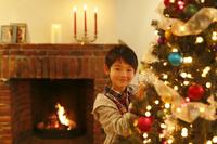 クリスマスツリーに飾り付けをする日本人の男の子