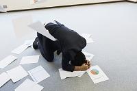 散らかった書類と日本人ビジネスマン