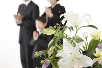 喪服姿で合掌する日本人家族と祭壇の花