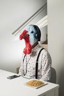 音楽を聴く鳥頭の男性