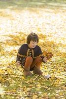 公園で銀杏の落ち葉を拾う女の子