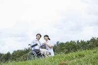車椅子に乗るシニア女性と介護士の女性