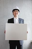メッセージボードを持つヘルメット姿の男性