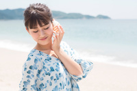 貝を耳に当てている日本人女性