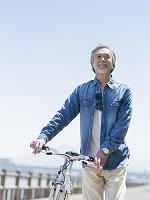 自転車を押すシニアの日本人男性
