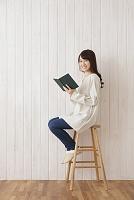 椅子に座って本を持つ日本人女性