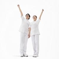 ガッツポーズをして立つ看護師