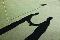 握手するゴルファーの影