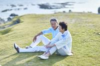 海辺でくつろぐ日本人シニア夫婦
