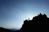 岩山を登る男性のシルエット ハイキング