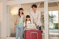 ホテルの入り口でカートを押す家族