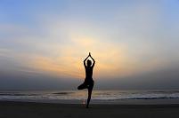 インド ケララ州 砂浜でヨガをする女性