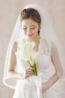 花を持ったウェディングドレス姿の女性