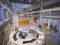 素粒子加速器の上に立つ科学者