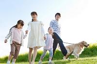 手を繋いで歩く日本人家族と犬